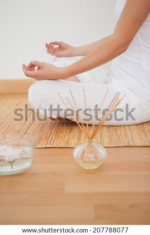Peaceful woman sitting in lotus pose on bamboo mat at home against a white wall - stock photo