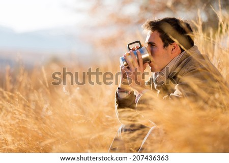 peaceful young man drinking coffee in autumn by the lake - stock photo
