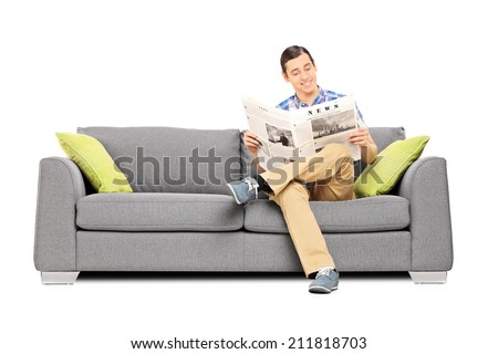 Peaceful young man reading the news seated on sofa isolated on white background - stock photo