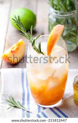 Peach and rosemary fizz cocktail on a wooden background. - stock photo