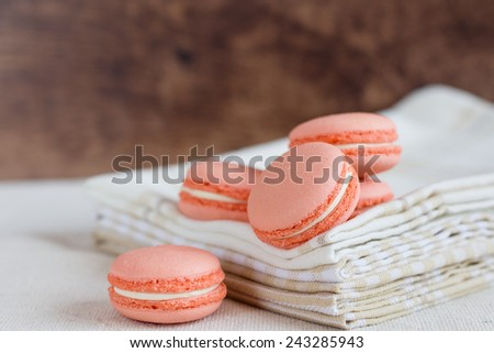 Peach color macaroons on rustic background. Shallow focus - stock photo