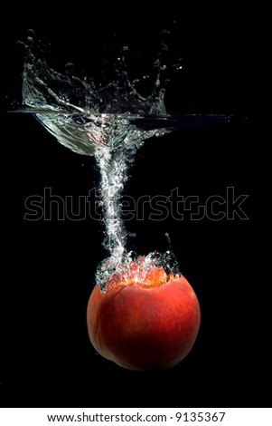 Peach dropped into water with bubbles - stock photo