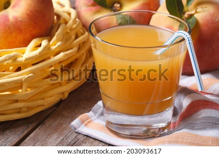 peach juice in glass closeup on a table on a background of fruit. horizontal  - stock photo
