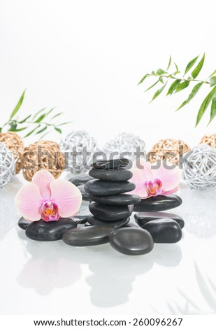 Peach Moth orchids, black zen stones with silver and gold twig balls at the background  - stock photo