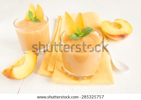 Peach smoothie dessert with mint on napkin, top view - stock photo