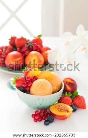 Peach sorbet and fresh berries, selective focus - stock photo