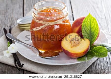 Peach vanilla jam with fresh peaches on table - stock photo
