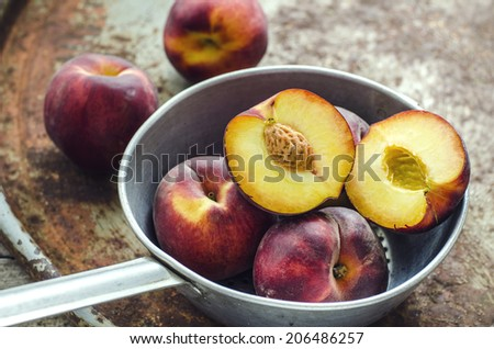 Peaches in aluminum dipper in the old surface. Rustic style - stock photo