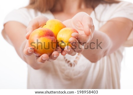 peaches in female hand, isolated on white background - stock photo