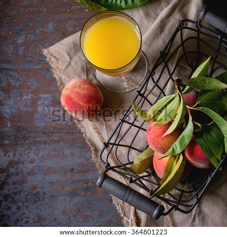 Peaches on branch with leaves in metal basket and glass with peach juice over gray textile napkin. Over old metal background. Dark rustic style. Top view. Square image - stock photo