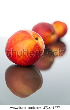 Peaches on glass sheet with backlight, vertical, front view. - stock photo