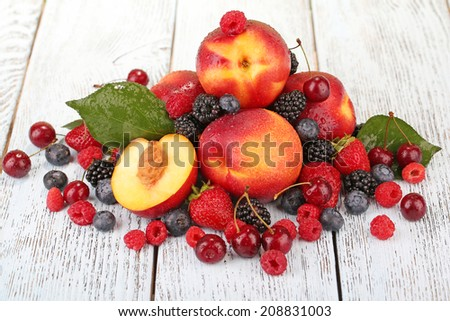 Peaches with berries on wooden table close-up - stock photo