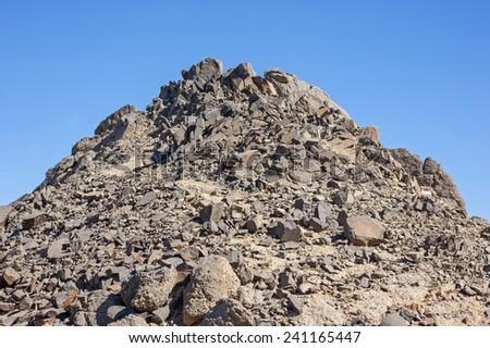 Peak of rocky granite mountain in arid desert landscape against blue sky background - stock photo