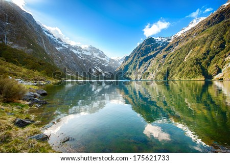 Peaks of Darran Mountains reflecting in a Lake Marian, Fiordland national park, New Zealand South island - stock photo