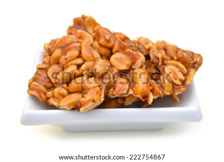 Peanut brittle in white plate isolated  - stock photo