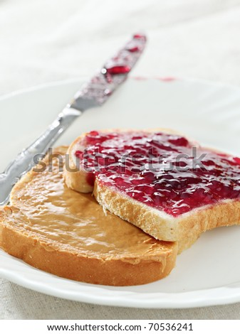 Peanut butter and jelly on pieces of bread. - stock photo