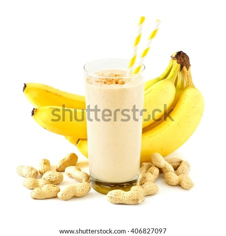 Peanut butter banana smoothie in a glass with straws and scattered peanuts and bananas over white - stock photo