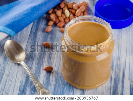 Peanut butter in a jar on a blue background.  Shallow dof. - stock photo