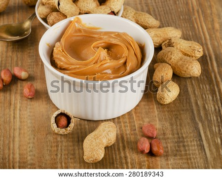 Peanut butter in a white bowl with peanuts.  Shallow dof. - stock photo