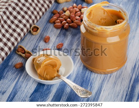 Peanut butter in  spoon  with peanuts.  Shallow dof. - stock photo