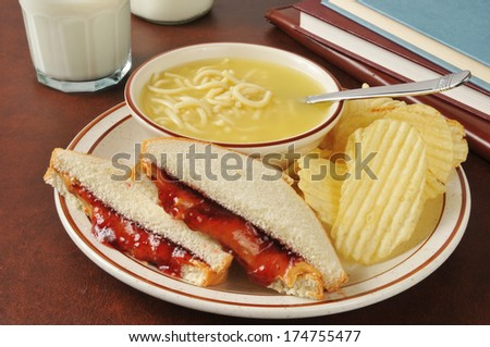 Peanut butter sandwich with chicken noodle soup and school books - stock photo