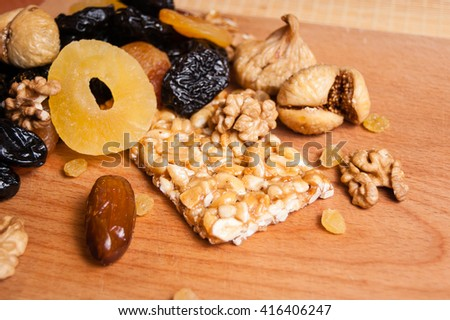 peanuts honey, candied roasted nuts, Grilyazh, dried fruits, dried pineapple, dried figs, walnuts, prunes, figs, dried apricots, candied roasted nuts on the table  - stock photo