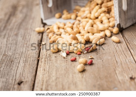 Peanuts in shells in the box on wood background. Also available in vertical format. - stock photo