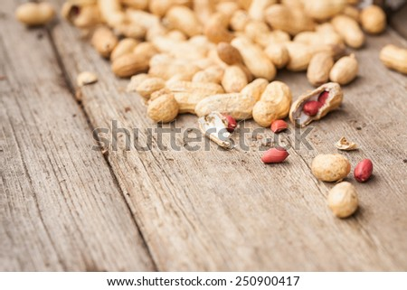 Peanuts in shells on wood background. Also available in vertical format. - stock photo