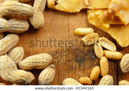 Peanuts in the shell and out laying on a wooden table. - stock photo