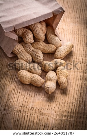 peanuts poured from paper bag on wooden board food and drink still life  - stock photo