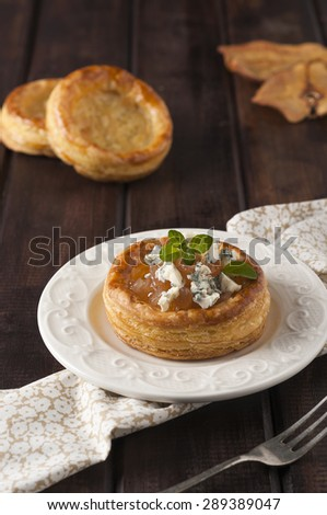Pear and gorgonzola puff pastry basket on dark wood table - stock photo