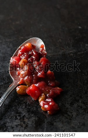 Pear cranberry relish in spoon over dark background, copy space, selective focus - stock photo