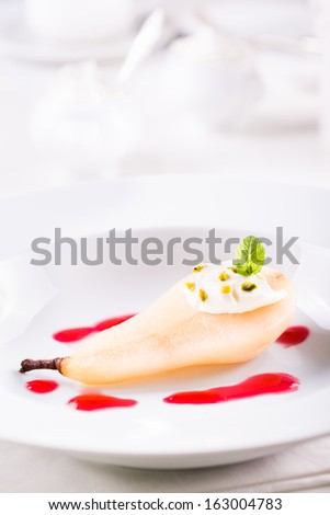 Pear poached in amaretto with cranberry sauce - stock photo