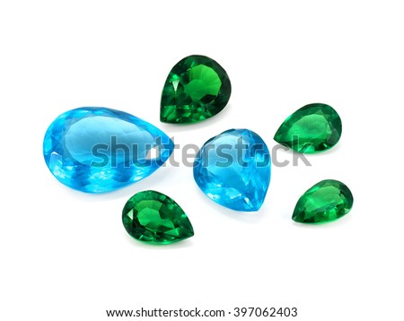 Pear shaped blue topaz and emeralds on a white background. Natural Gemstones.
