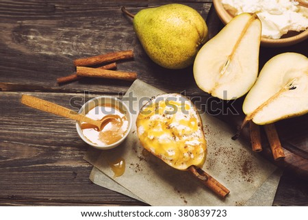 Pear with ricotta cheese, honey and cinnamon on rustic wooden background. Healthy and diet food. Top view. - stock photo
