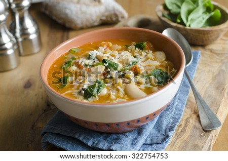 Pearl barley, butter bean and chickpea soup topped with shaved Parmesan - stock photo