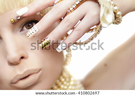 Pearl manicure with rhinestones on a gold background and pastel nails on female hand with decoration. - stock photo