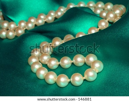 Pearl necklace on green satin background - stock photo