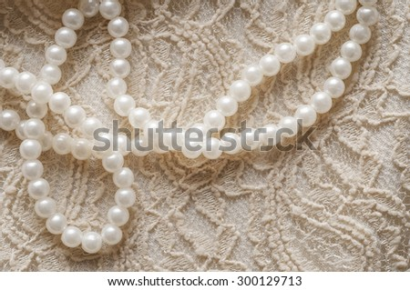 Pearl necklace on lace clothes background. - stock photo
