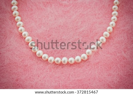Pearl necklace on pink sweater. - stock photo