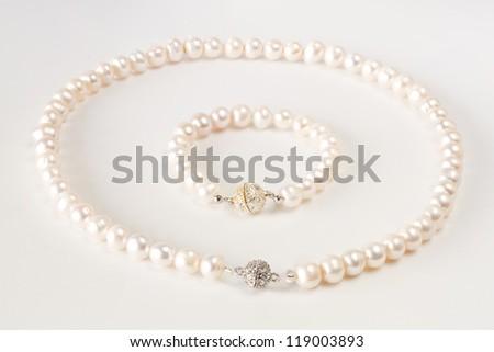 Pearls necklace bracelet on white background - stock photo