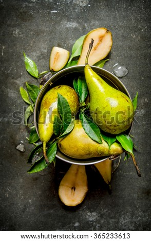 Pears in a bucket with leaves and ice. On the stone table. Top view - stock photo
