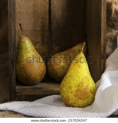 Pears in rustic setting with wooden box and hessian sack - stock photo