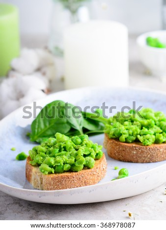 Peas on grilled toasts - stock photo