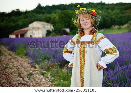 Peasant girl in a flowers wreath dressed in a russians gown stands on the dirt road along lavender field, farmhouse on background. Cross-processing from RAW file  - stock photo