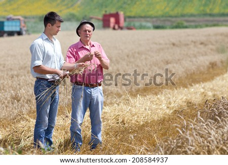 Peasant showing wheat ears to the business partner on the field - stock photo