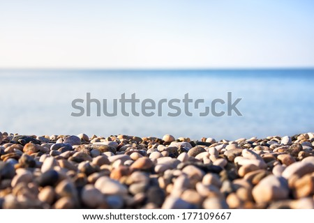 Pebble beach and blue sky on background - stock photo