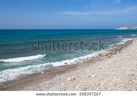 Pebble beach and blue water of the Mediterranean Sea. - stock photo