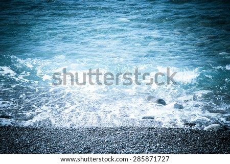 Pebble beach and blue water of the Mediterranean Sea. Toned. - stock photo