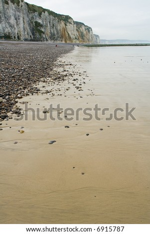 Pebble beach and shoreline at the Alabaster Coast in Dieppe, France. Reflections on a wet sand surface. - stock photo